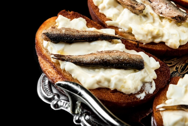 Sandwich with sprats, eggs and mayonnaise on black surface.