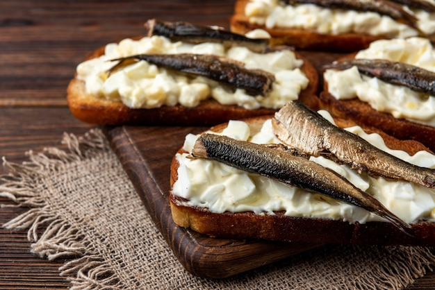 Sandwich with sprats, eggs and mayonnaise on wooden table.