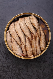 Бутерброд со шпротами на черном фоне