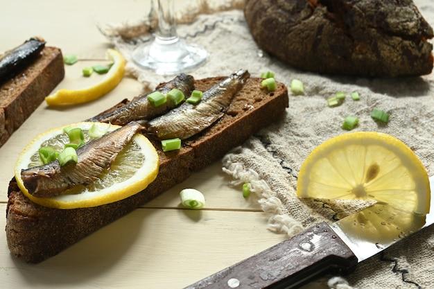 Бутерброд со шпротами. килька в масле. на деревянном фоне.