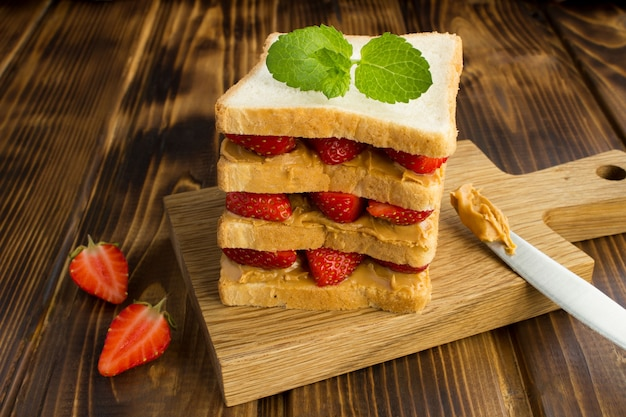 Sandwich with strawberries and peanut butter on the kitchen board