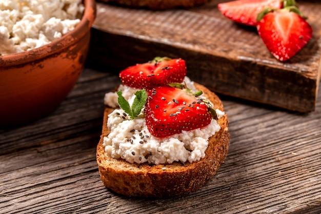 Бутерброд с клубникой, мягким сыром рикотта и медом, чиа на деревянном фоне