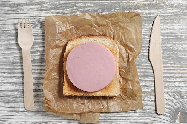 오래된 나무 테이블에 구운 빵과 소시지를 넣은 샌드위치, 위쪽