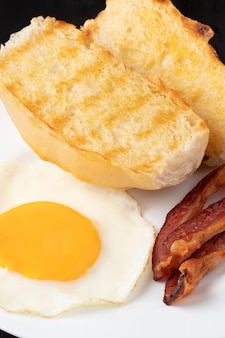 Sandwich with toasted french bread, egg and bacon.