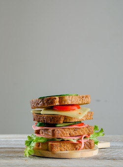 Sandwich with tomato, cucumber, cheese, sausage, greens on a cutting board on wooden and grey table, side view.