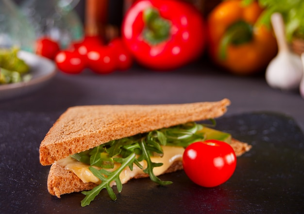 Sandwich with turkey breast, cheese, lettuce, arugula, tomatoes and onion on a black plate