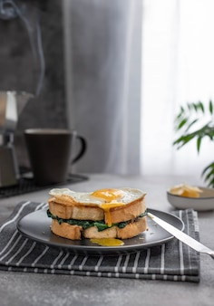 A sandwich with a yolk flowing from a fried egg. delicious breakfast sandwich with spinach and coffee maker with hot coffee.