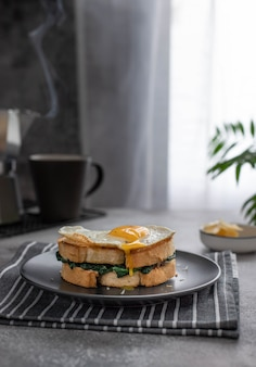 A sandwich with a yolk flowing from a fried egg
