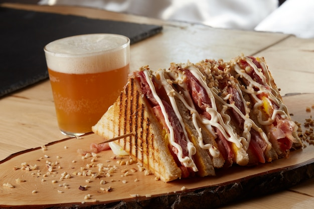 Sandwich on a wood tray with a beer