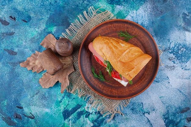 Sandwich on wooden plate on burlap napkin on blue.