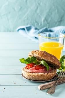 Сэндвич с говядиной, свежими помидорами и салатом ягненка, мультизерновая булочка на синей деревянной поверхности