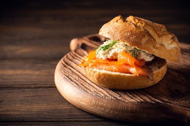 Бутерброд с лососем и маслом из зелени на старом деревянном столе