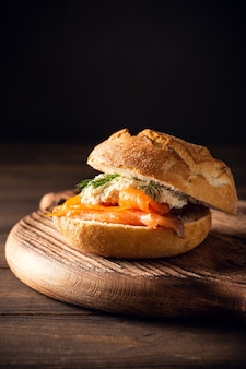 Sandwiche with salmon and herb butter on old wooden table