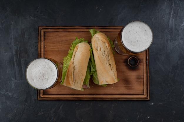 Бутерброды и пиво на деревянном столе