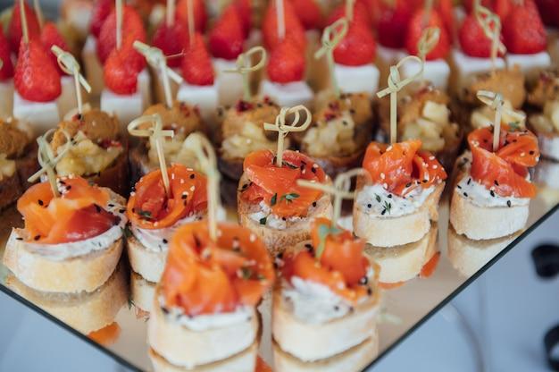 축제 테이블에 샌드위치, 카나페 및 케이크. 다양한 간식. 채식주의 자 포함