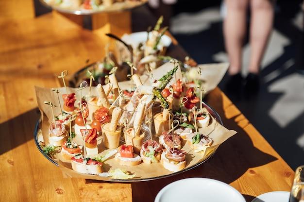 お祝いのテーブルの上のサンドイッチカナッペとケーキ多種多様なスナック