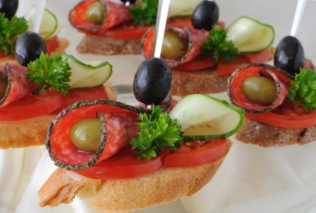 접시에 올리브와 살라미 소시지의 샌드위치 카나페