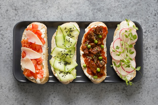 Sandwiches on ciabatta toast with fresh vegetables, radishes, tomatoes, cucumbers and microgreens. view from above.