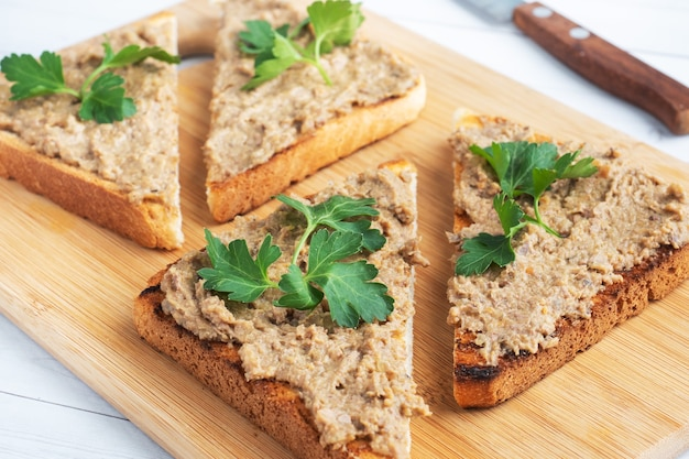 Sandwiches crispy toast and chicken liver pate with parsley leaves on a wooden cutting board