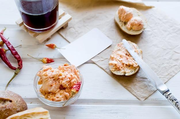 Бутерброды на завтрак со сливочным маслом домашнего приготовления с помидорами, перцем и специями на столе