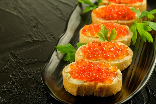 Sandwiches of fresh white bread with butter and fresh red caviar on the black dish