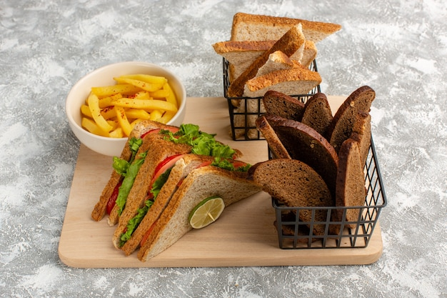 Sandwiches and fries along with different kinds of bread on grey