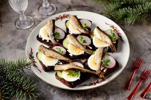 Sandwiches from baltic sprats on rye bread with cucumber radish and egg