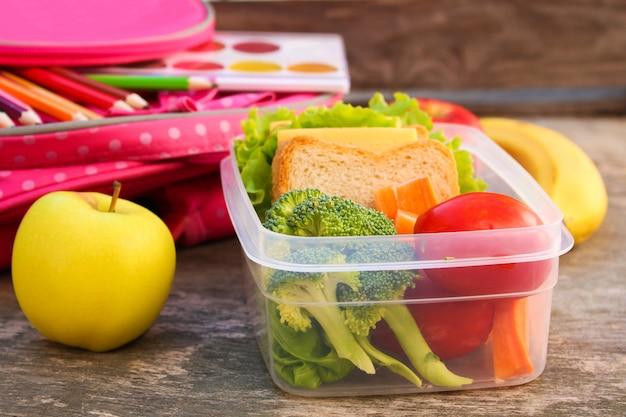 Бутерброды, фрукты и овощи в коробке еды, рюкзак на старых деревянных фоне.