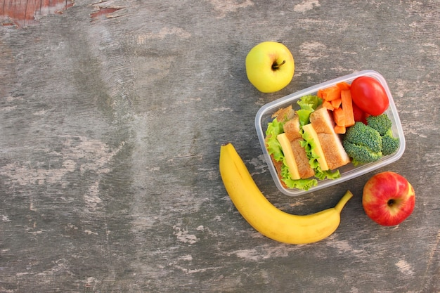 Sandwiches, fruits and vegetables in food box on old wooden background. top view. flat lay.