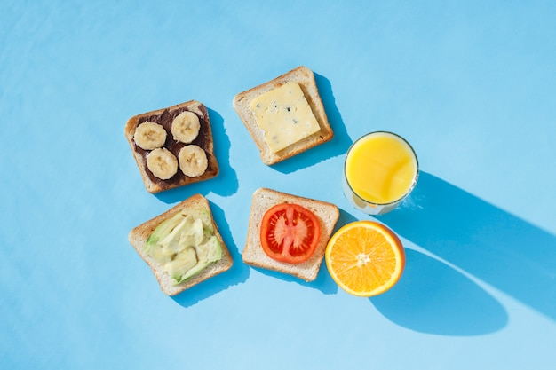 Sandwiches, glass with orange juice, oranges, blue surface. the  flat lay, top view.