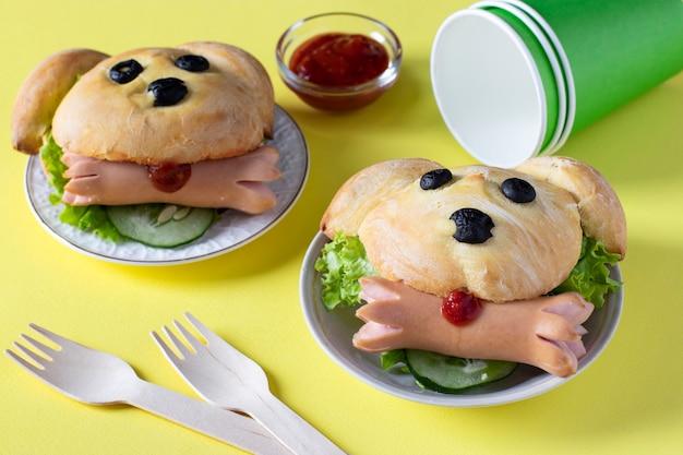 黄色の背景にソーセージと犬の形をしたサンドイッチ。子供のための料理のアイデア。閉じる