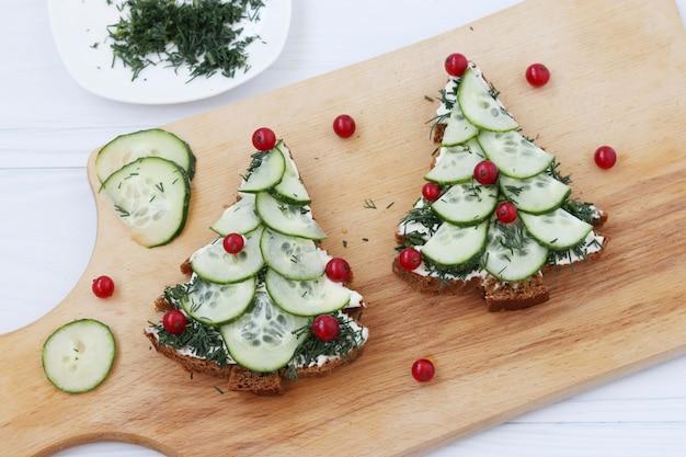 果実で飾られたクリスマスツリーの形の黒パン、チーズ、キュウリのサンドイッチ