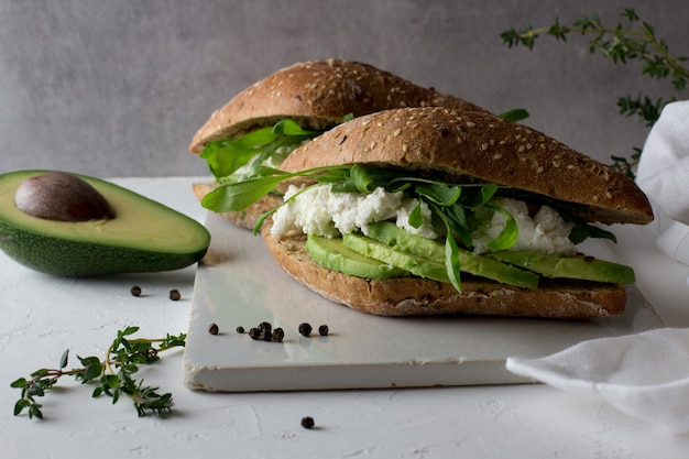 Sandwiches made of whole grain bread with avocado and ricotta cheese.