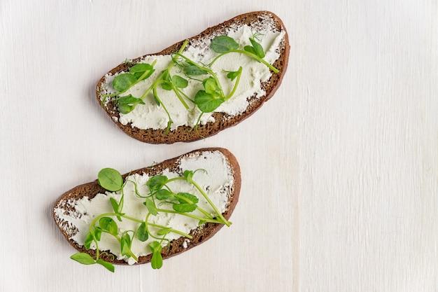 Бутерброды на ржаной тост с свежим горохом микрогрин и сливочный сыр на белом фоне.