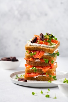 Sandwiches stack with smoked pink salmon olives, kalamata, microgreens and cream cheese on gray ceramic plate and trendy concrete table. traditional scandinavian toast. top view.