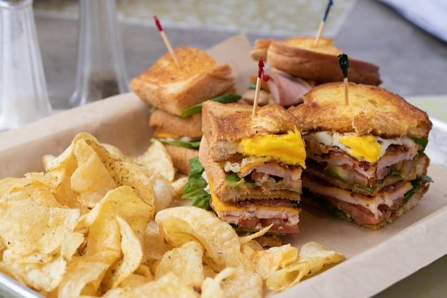 컨테이너에 있는 칩 옆에 양상추 햄과 치즈로 속을 채운 샌드위치