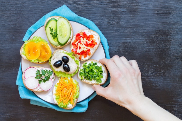 Sandwiches or tapas of their white bread with delicious healthy ingredients on a plate, on a black background.