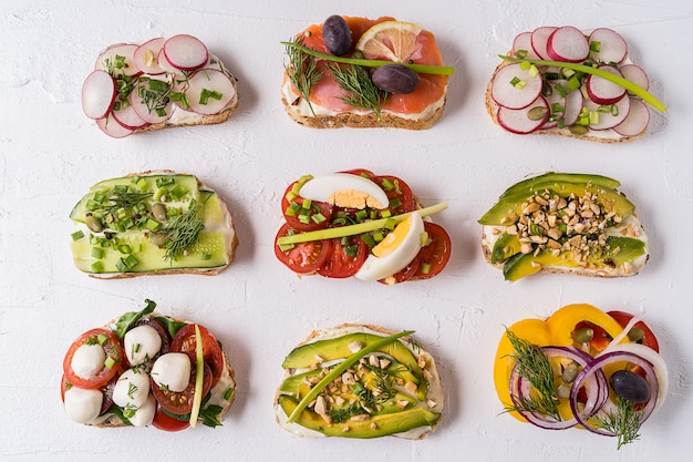 Sandwiches or tapas with bread , cream cheese, vegetable and tasty toppings.