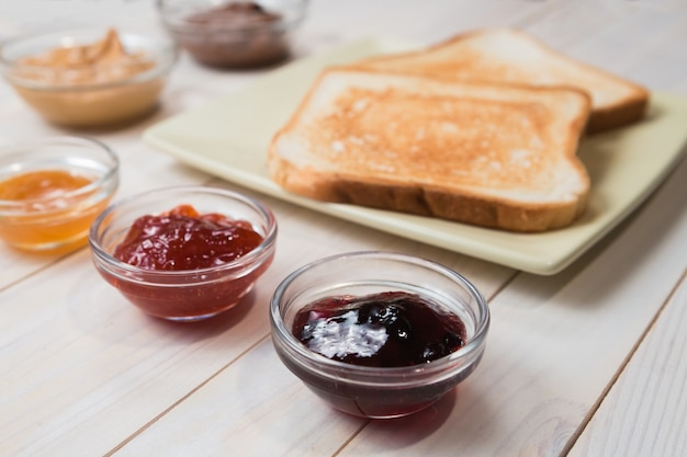 Sandwiches or toasts with peanut butter, chocolate paste and strawberry, currant and apricot jelly or jam on white wooden table, close up