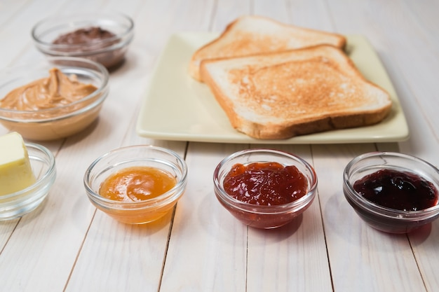 Sandwiches or toasts with peanut butter, chocolate paste and strawberry, currant and apricot jelly or jam on white wooden table