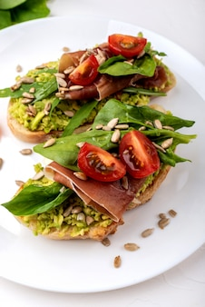 Sandwiches with avocado cream, tomatoes and jamon.