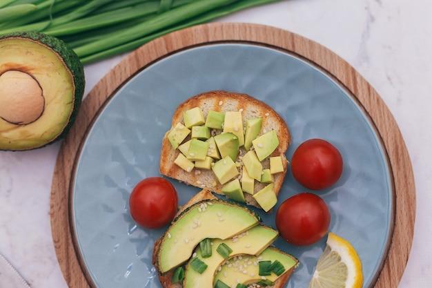 Бутерброды с авокадо, помидорами и зеленью на деревянном фоне на столе. концепция здорового питания и вегетарианства, правильный завтрак для хорошего пищеварения.