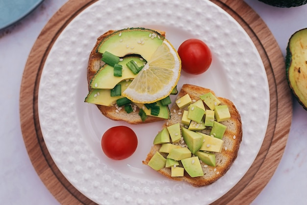 Sandwiches with avocado, tomatoes and herbs on a wooden background on the table. concept of healthy eating and vegetarianism, right breakfast for good digestion.