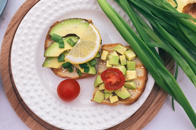 Sandwiches with avocado, tomatoes and herbs on a wooden background on the table. concept of healthy eating and vegetarianism, the right breakfast for good digestion.