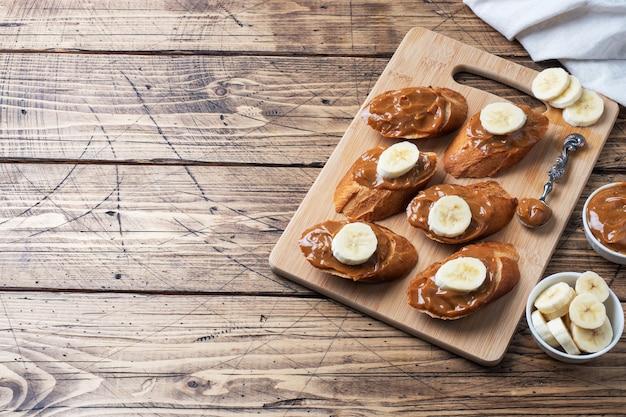 バゲットのパンのサンドイッチは、コンデンスミルクとバナナの甘いペーストで広がります。木製のテーブル。スペースをコピーします。