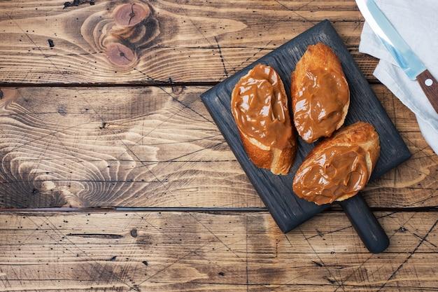 Бутерброды с багетом из хлеба намазать сладкой пастой из вареного сгущенного молока. деревянный стол. копировать пространство