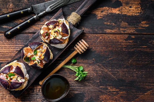 Sandwiches with baked figs, jam and cream cheese. wooden background