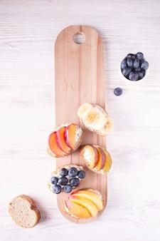 木の板にベリーとフルーツのサンドイッチ