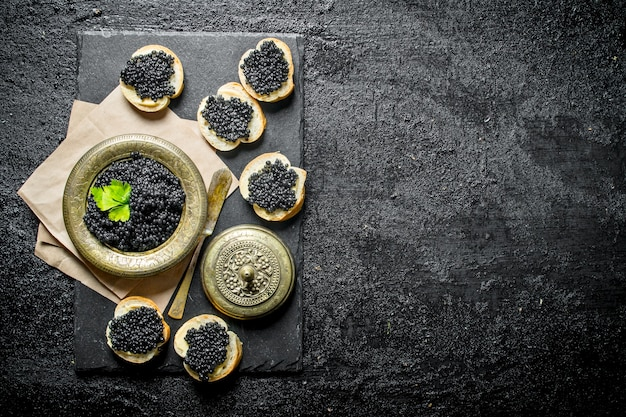 Sandwiches with black caviar and caviar in a bowl on paper with parsley. on black rustic