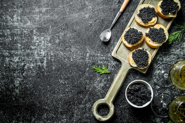 Sandwiches with black caviar, caviar in a bowl and white wine. on black rustic